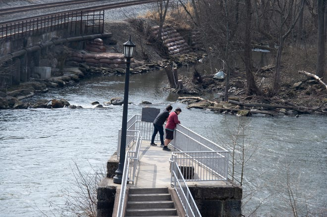 People watch the Cuyahoga River below at Franklin Mills Riveredge Park in downtown Kent.