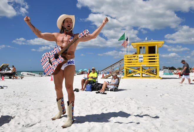 Robert Burck, also known as The Naked Cowboy, entertains beach-goers Tuesday afternoon on Siesta Beach.
