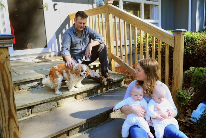In this Thursday, March 26, 2020 photo, Elizabeth and Chris Tillett pose with their twin sons, John and Luke, and their dog Ellie at their then home in Wilton, Conn. Chris Tillett, who now lives in Virginia, was one of the first coronavirus patients in Connecticut. He says he is still coping with health problems a year after become the first Connecticut resident to be diagnosed with COVID-19, but the experience has brought a new optimism to life. (Christian Abraham/Hearst Connecticut Media, File)