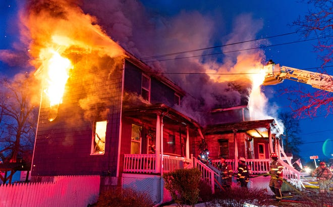 Firefighters withdraw from inside a home during a three-alarm fire at 180 Spring St. in Winchendon early Monday night.