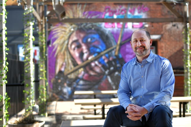 Gary Benacquista in the courtyard area of the Beer Garden Tuesday with a PowWow! mural behind him.