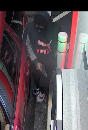 Fayetteville police say this masked gunman and a second man robbed a person using the ATM at Cross Creek Mall on Feb. 19.