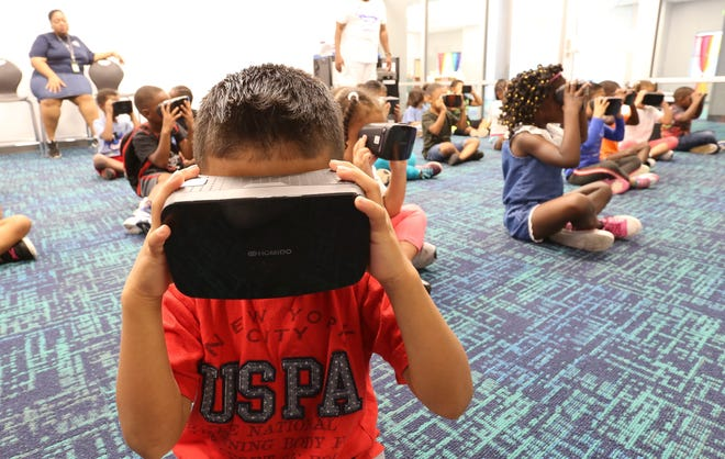 Benny Hernandez Ventura looks through virtual reality goggles as he and fellow students take a virtual trip to the Great Barrier Reef in Australia during the summer  learning program at Skyland Elementary School Friday, June 21, 2019. [Staff Photo/Gary Cosby Jr.]