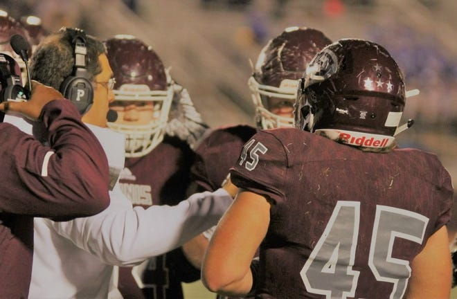 Former Ennis offensive coordinator Tony Castillo (in white) is surrounded by his offensive players during a game this season. Castillo has been hired as head football coach and campus coordinator at Carrollton Creekview.