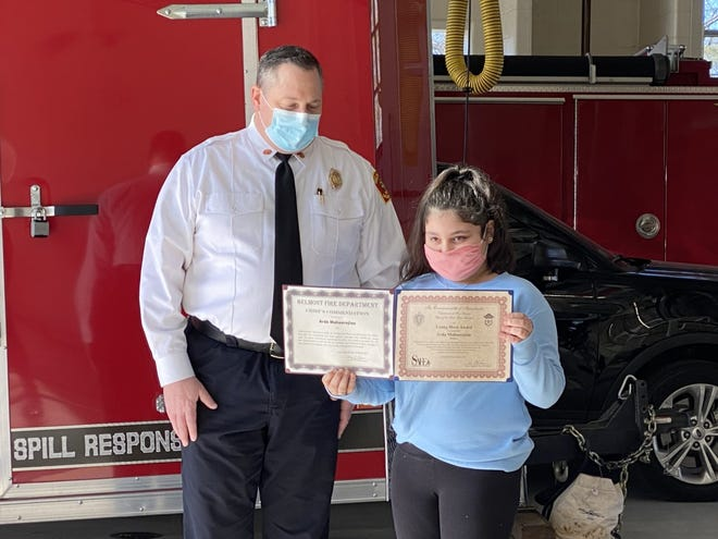 """Acting Fire Chief Wayne Haley with 9-year-old Arda Mahserejian of Belmont, who was recognized with a """"Young Hero Award"""" by the Belmont Fire Department and the Massachusetts Fire Marshall on March 8, 2021."""