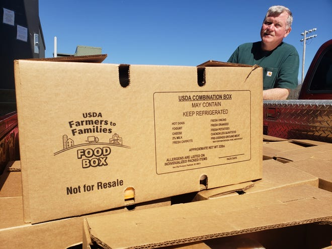 Steve Metcalf, a volunteer with Paint Fork Baptist Church, loads 40-pound boxes of food into his truck to deliver directly to families who need them on March 4, 2021.