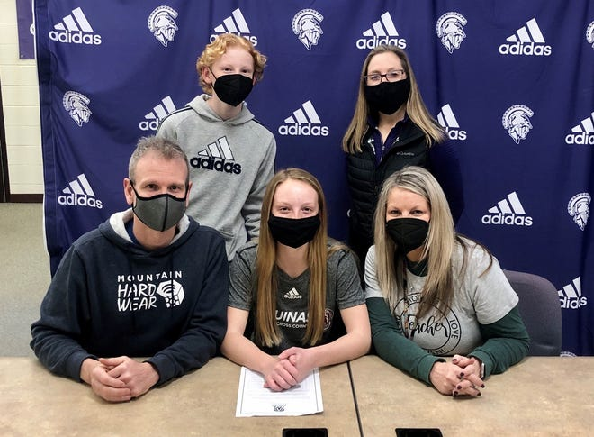 Lakeview track and cross country standout Genevieve Moore has committed to compete at Aquinas College. She is joined by her family and Lakeview coach Becky Pryor.