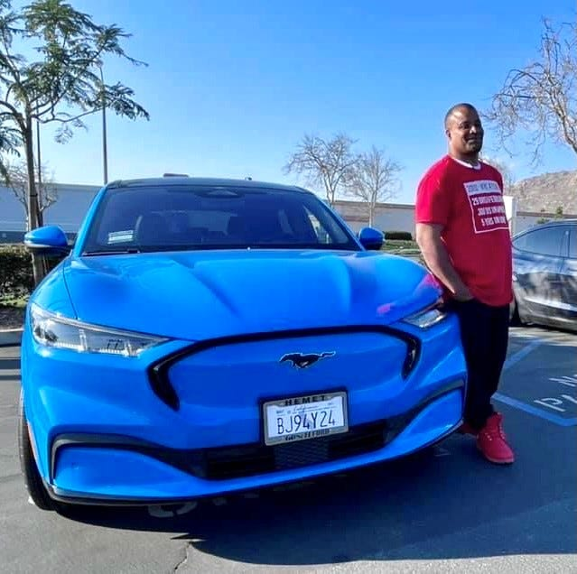 Sergio Rodriguez of Saint Marys, Georgia is seen here with his 2021 Ford Mustang Mach-E on February 20, 2021 using the ChargePoint charger in Riverside, California during this cross-country trip. A friend nearby is using the Tesla supercharger.
