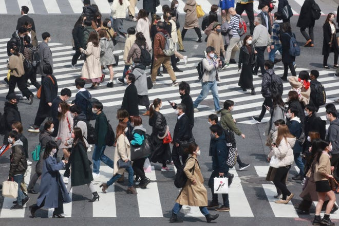 People wearing face masks to protect against the spread of the coronavirus cross a scramble intersection in Tokyo on March 9, 2021.