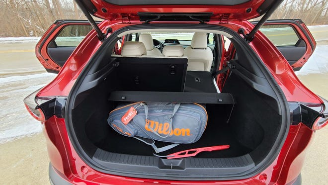 The 2021 Mazda CX-30 Turbo is a subcompact SUV with hatchback cargo room behind the rear seats. The seats also fold flat for more cargo space.