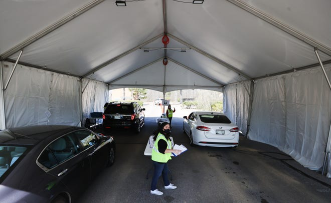 Volunteer Jonni Holdswortch checks in drivers before they are given their COVID-19 vaccine at the Germantown Baptist site on Tuesday, March 9, 2021. The site is set up to serve around 1500 appointments daily from 9am to 6pm.