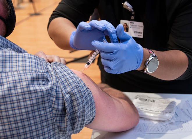 Registered nurse Penny Brown, right, gives a COVID-19 vaccine to Jason Kirk at the Brownsville Community Center in Pensacola, Fla., on Monday, March 8, 2021.