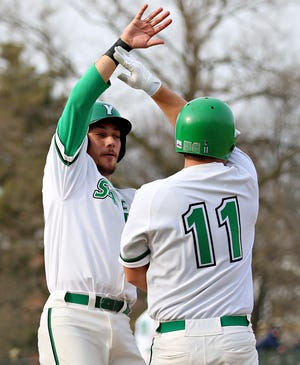 York College's Joe Capobianco, left, and Jack Barry celebrate consecutive runs against Lebanon Valley during season opener baseball action at York College of Pennsylvania in Spring Garden Township, Tuesday, March 9, 2021. York College would score nine runs on eight hits in the first inning. Dawn J. Sagert photo