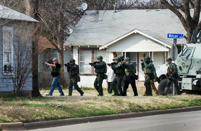Wichita Falls police SWAT search a house on Wilson Street after arresting murder suspect Christopher Payne Monday afternoon.