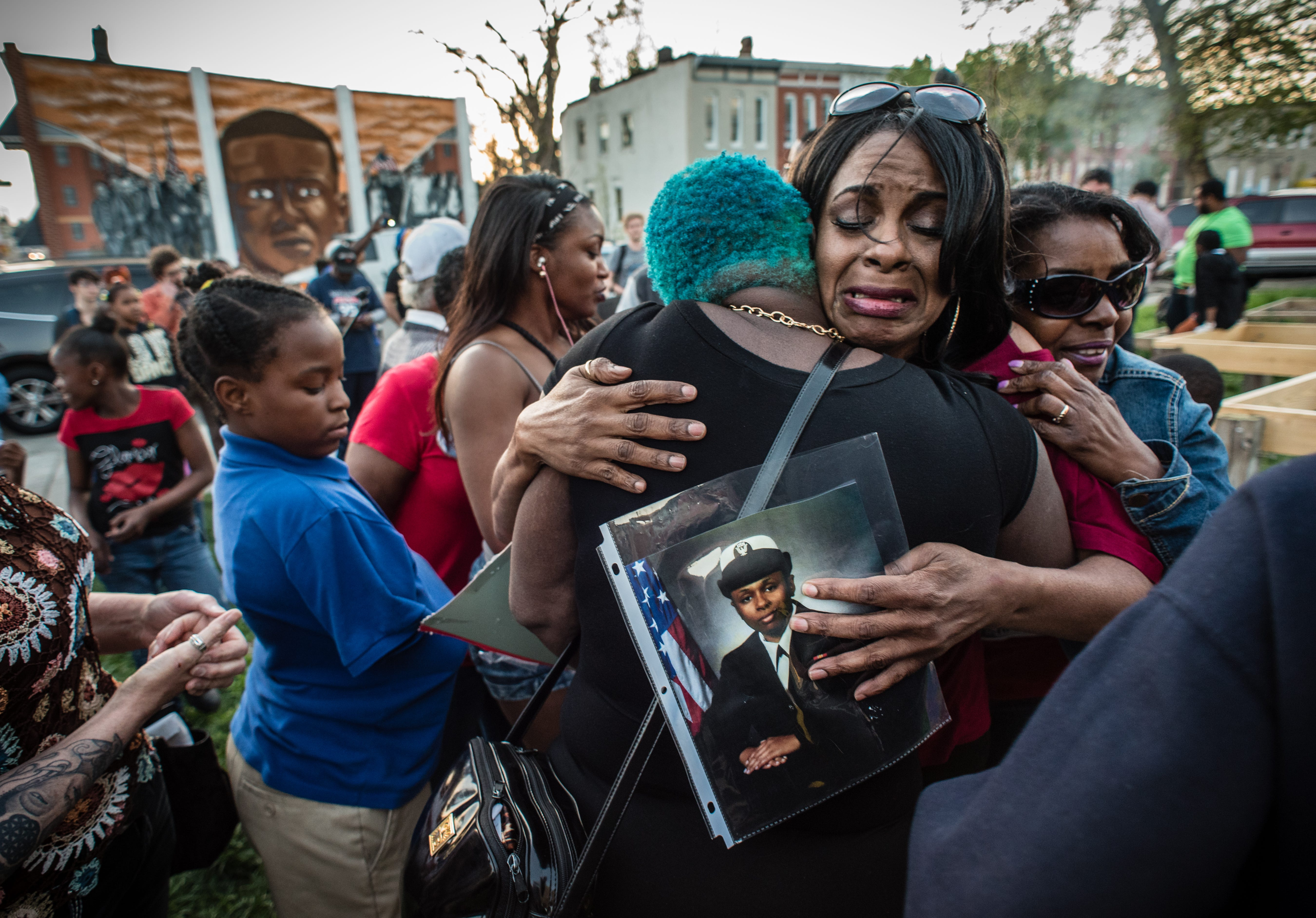 Activist Gina Best, weeps after speaking to an assembly on April 19, 2016 in Baltimore about her daughter, India Kager, who was killed by police in Virginia Beach. She's embraced by friends, supporters and residents after her emotional testimony.