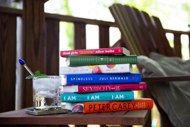A stack of summer reading on a porch.