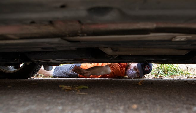 Chris Chuter points to where his car's catalytic converter should be. The part was stolen the day before. Austin police say thieves are increasingly targeting catalytic converters, which can be sawed off quickly and contain valuable metals that have been going up in price.