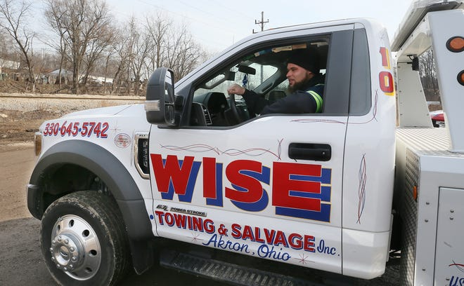 "Will Wise, 29, owner of Wise Towing & Salvage, pulls out in his ""baby,"" a new Ford F550 wrecker, one of four tow trucks he owns."