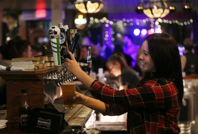 A bartender pours beer at Sully's Irish Pub in Medina in 2019. [Beacon Journal file photo]