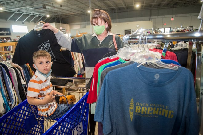 """Mary Fuller and her grandson, Christopher Fuller, 3, check out the leftover """"We Give A Shirt"""" T-shirts for sale Wednesday at the Catholic Social Services thrift store in Augusta."""