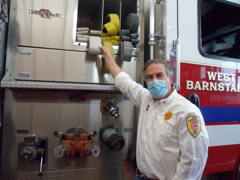 Fire Chief Joseph Maruca explains the finer points of fire hose capacity on one of the department's fire trucks.