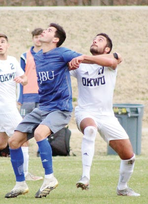 Oklahoma Wesleyan University's Alfeu Bertini, right, tussles with a John Brown University player for position during Tuesday's men's soccer battle in Bartlesville.
