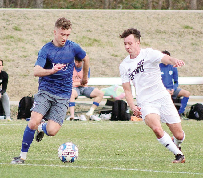 Oklahoma Wesleyan University's Pol Mur, right, challenges a John Brown University player during fierce men's soccer play Tuesday in Bartlesville. The teams tied, 1-1.