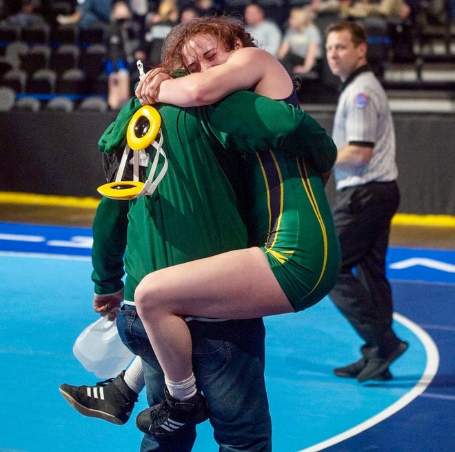 Rock Bridge junior Anna Stephens, right, leaps into the arms of coach Robin Watkins after winning the 132-pound fifth-place match Tuesday during the girls state wrestling championships at Cable Dahmer Arena in Independence.