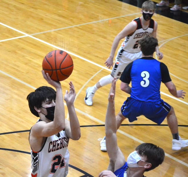 Cheboygan senior center Jacob Grondin (left) puts up a shot over Inland Lakes junior center Austin Brege during the first half of a varsity boys basketball contest in Cheboygan on Tuesday.