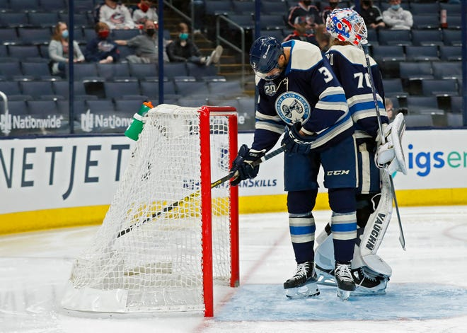 Columbus Blue Jackets defenseman Seth Jones (3) digs out the puck from the net after Florida Panthers right wing Patric Hornqvist (70) scored on goaltender Joonas Korpisalo (70) during the second period of their NHL game at Nationwide Arena in Columbus, Ohio on March 9, 2021.