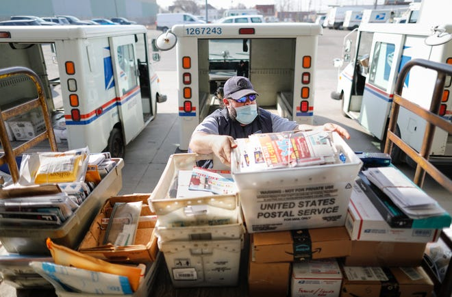 Postal worker Tony Sobony, 43, loads his delivery truck with mail and packages on the loading dock behind the South Columbus branch of the United States Postal Service. A mail carrier for 21 years, Sobony said there's nothing he'd rather do despite the COVID-19 pandemic and other challenges of the past year.