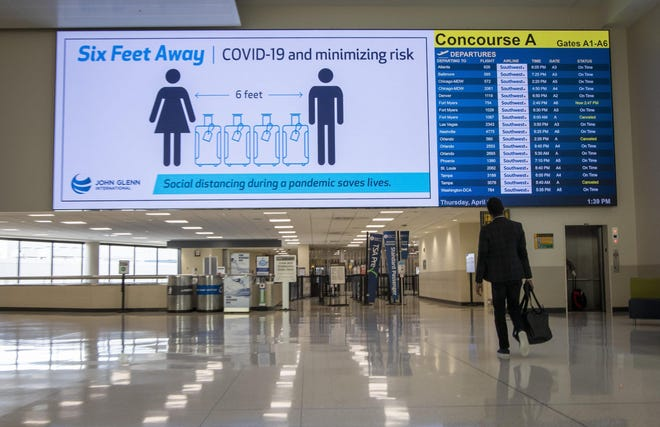 A video board warns travelers to maintain a six-foot distance inside John Glenn International Airport in Columbus on Thursday, April 2, 2020.