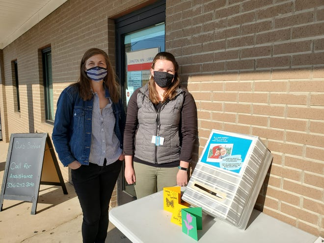 Davidson County Public Library employees Emma Welch (left) and Bethany Geiger stand next to a box where the public can drop off cards they make or purchase with a note of encouragement written inside for residents of Alston Brook nursing home and rehabilitation center.