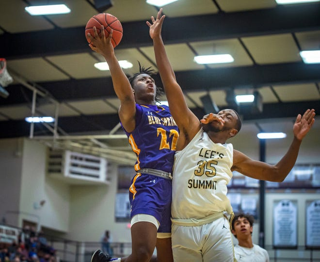 Lee's Summit defender Bud Crawford (35) takes a hand to the face from Blue Springs forward Ikenna Ezeogu (22) as Ezeogu goes up for a shot in a Class 6 sectional playoff Tuesday. Lee's Summit claimed a 66-61 win.