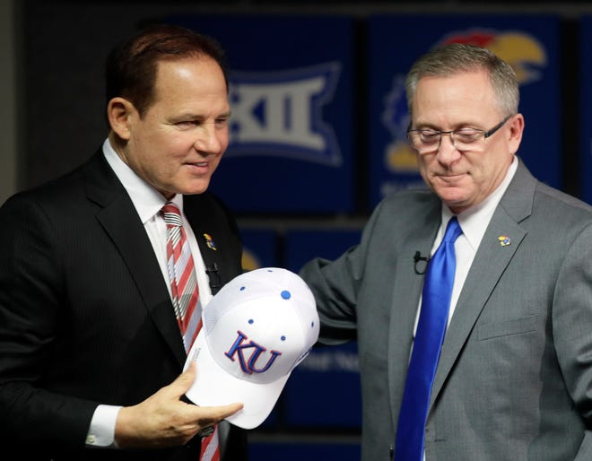 Les Miles, left, is introduced as Kansas football coach by athletic director Jeff Long, right, during a news conference in Lawrence, Kan. Kansas has fired athletic director Jeff Long less than two days after mutually parting with Les Miles amid sexual misconduct allegations dating to the football coach's time at LSU, a person familiar with the decision told The Associated Press Wednesday.
