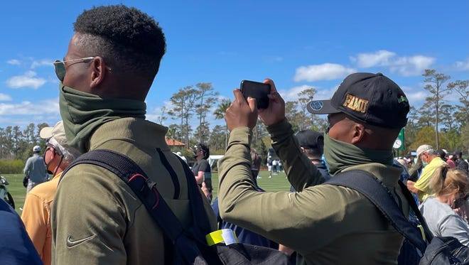 Florida A&M golf team members Marcus and Miles Taylor, twins who hail from South Africa, watch PGA Tour players Dustin Johnson and Phil Mickelson hit practice balls on Wednesday during their team's tour of The Players Championship.