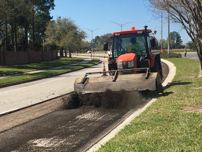 A construction worker prepares a section of Gate  Parkway in Jacksonville for a fresh layer of asphalt.