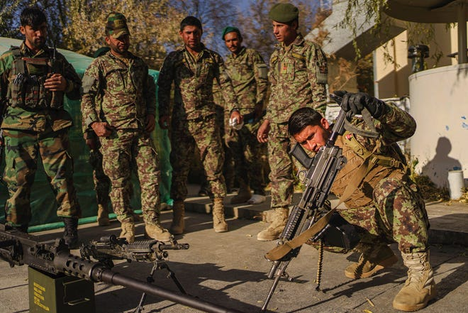 Soldiers from the Afghan National Army's quick reaction force inspect and clean their weapons at their base on the outskirts of Maidan Shahr, Afghanistan, on Nov. 7, 2020.