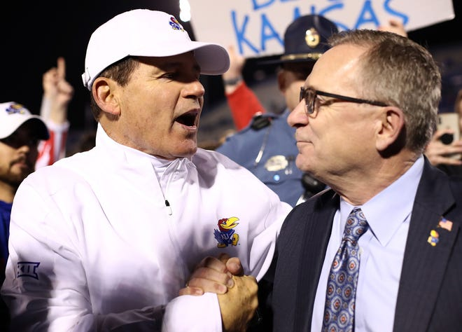 Kansas head coach Les Miles and Athletic Director Jeff Long congratulate each other after the Jayhawks defeated Texas Tech, 37-34, on Oct. 26, 2019, in Lawrence, Kans.