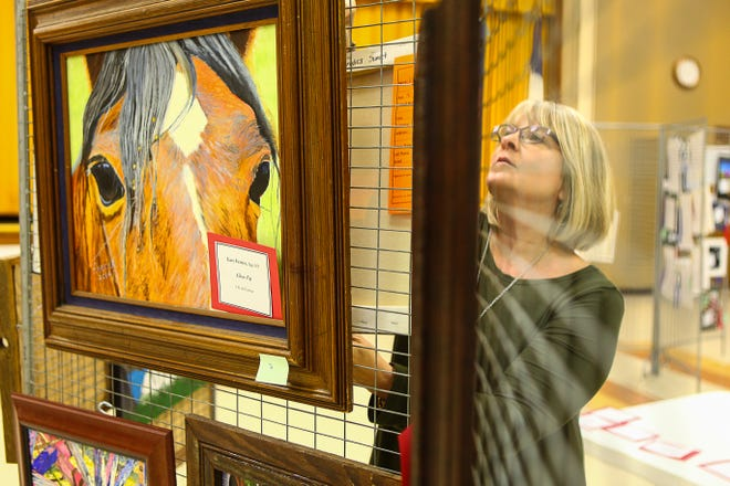 Penny Renfroe hangs a painting during set up for the Shauney P. Lucas Memorial Art Show in Whitesboro in 2016.