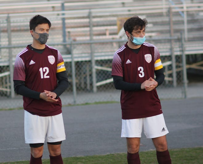 Dixon seniors Jacob Martin, left, and Walker Brinson wait for their names to be called before their soccer match against Richlands on Monday. The two also use their kicking abilities for the Bulldogs' football team. [Chris Miller / The Daily News]