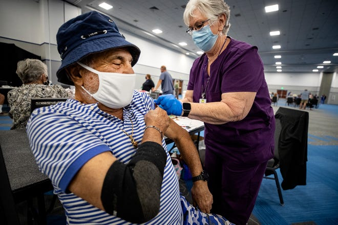 Florida Department of Health in Polk County will hold a free vaccination clinic in Haines City this Friday, from 10 a.m. - 6 p.m, no appointment necessary.  At left, Meyer Gaday gets his Moderna shot administered by Registered Nurse Dianne Accetta during the health department's mega vaccination event held in March at the RP Funding Center in Lakeland Fl. Wednesday  ERNST PETERS/ THE LEDGER