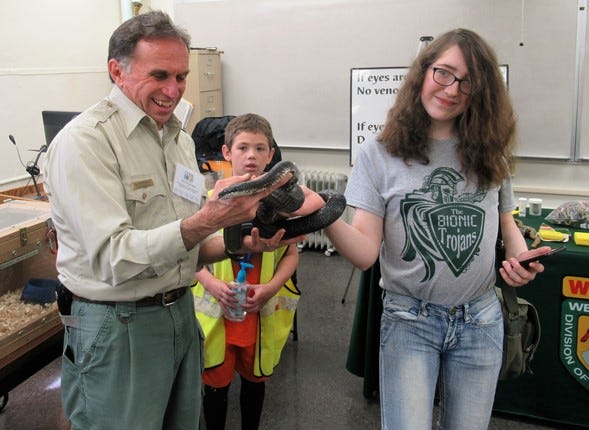 """Kylee Timbrook (right) got the opportunity to touch a snake during one of Mineral County's prior STEM festivals. Jim Freganaro, wildlife biologist with the West Virginia Division of Natural Resources will be a presenter during this year's Virtual STEM Festival to be held Saturday, March 13. Participants will get to """"hear"""" like a snake and will learn the differences between poisonous and non-poisonous snakes. Those wishing to register online may still do so at mineralstem.com."""