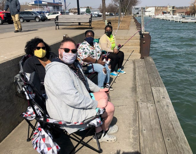 SUNY Brockport students Lucas Hunsucker, Ashley Mitchell, Lahenza Lamour and Adeola Akihyemi take a break from the books and enjoy a morning of fishing on the City Pier in Canandaigua.