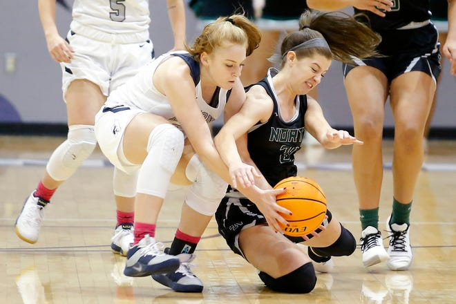 Edmond North's Laci Steele, left, and Norman North's Keely Hunt go for the ball during a high school basketball game between Edmond North and Norman North in Edmond, Okla., Tuesday, Jan. 7, 2020.