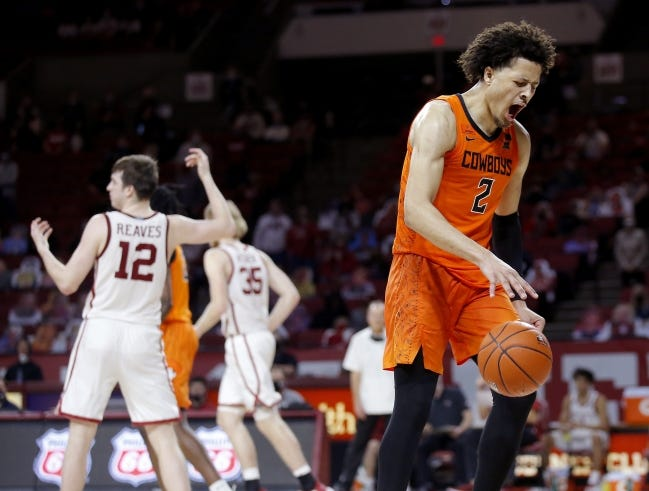 OSU's Cade Cunningham (2) celebrates after being fouled by OU's Austin Reaves (12) in overtime of a 94-90 win Feb. 27 at Lloyd Noble Center in Norman.