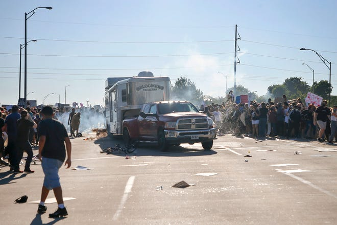 A pickup drives through a group of protesters who shut down Interstate 244 during a rally May 31 in Tulsa. The march was to mark the anniversary of the Tulsa race massacre in 1921 and to protest the killing of George Floyd in Minneapolis.