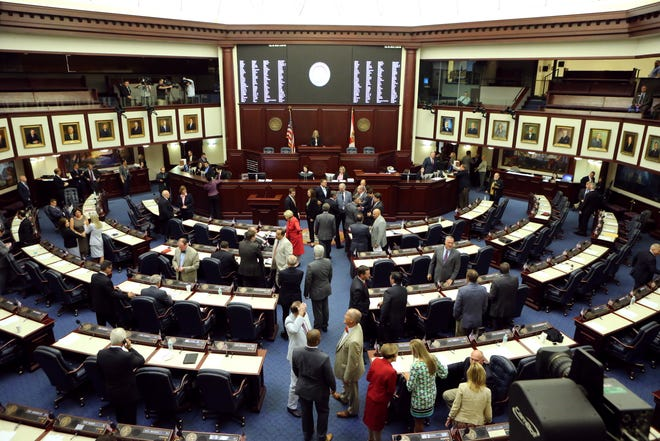 Florida representatives greet each other on the house floor prior to the start of the special session in 2015 in Tallahassee.