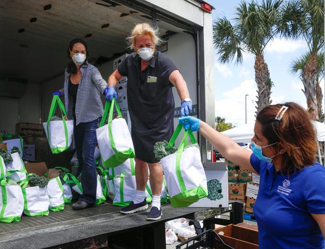 Margaret Duriez (left) and Lily Holt Dillon hand bags of food to Soniann Balasquide on March 20, 2020. The food bags would later be given to families of children who are members of the Max M. Fisher Boys & Girls Club in Riviera Beach.