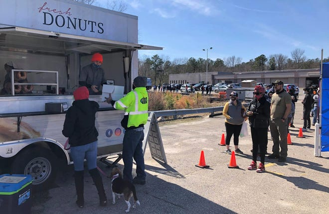 Mrs. Yoder's Kitchen fans wait in line to purchase donuts at the Colonial Heights Farmers Market on March 6, 2021.